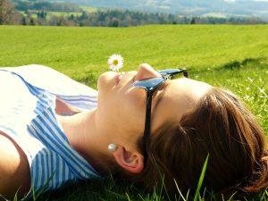 Schluss mit Keine zeit fuer mich - Frau liegt auf der Wiese in der Sonne